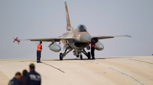 FILE - In this Monday, Nov 25, 2013, file photo, technicians inspect an Israeli air force F-16 jet at the Ovda airbase near Eilat, southern Israel. (AP Photo/Ariel Schalit, File)