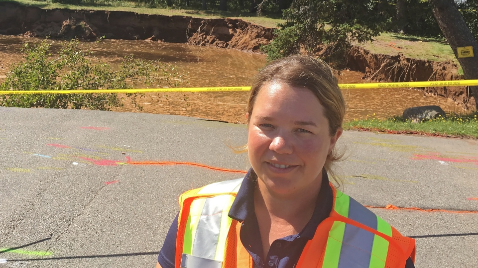 Nova Scotia Regional Geologist Amy Tizzard poses in front of a sinkhole in Oxford, N.S. on Monday, September 3, 2018. A large sinkhole in a sleepy Nova Scotia town appears to have stopped growing, at least for now, as officials continue to monitor the situation. (THE CANADIAN PRESS/Rob Roberts)