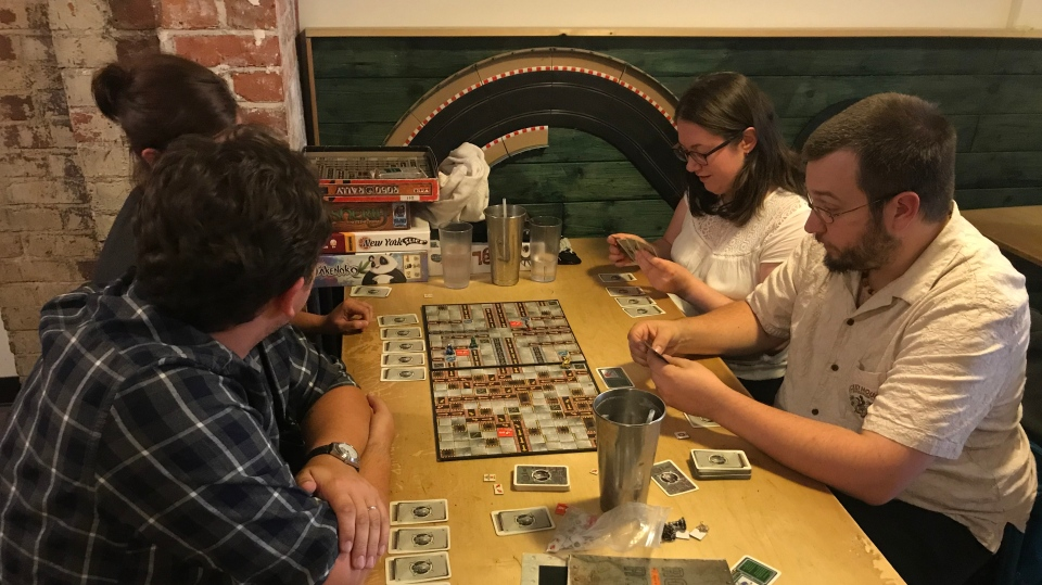 Doug Hancock, right, plays a board game with friends at Interactivity Board Game Cafe in Victoria. (CTV Vancouver Island)