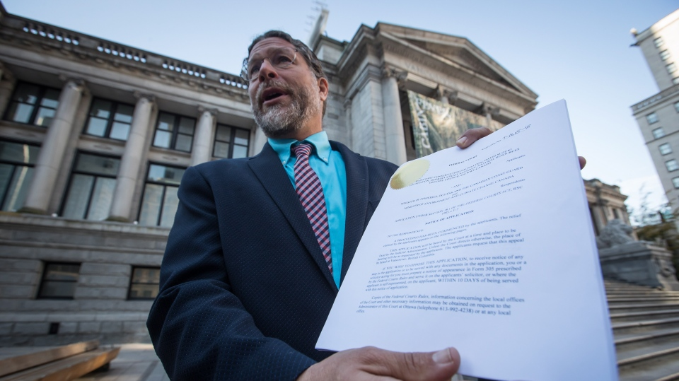 Jay Ritchlin, David Suzuki Foundation Director-General for Western Canada, holds a copy of a lawsuit conservation groups filed in federal court against Fisheries and Oceans Canada regarding the protection of southern resident killer whales, during a news conference in Vancouver, on Wednesday September 5, 2018. (THE CANADIAN PRESS/Darryl Dyck)