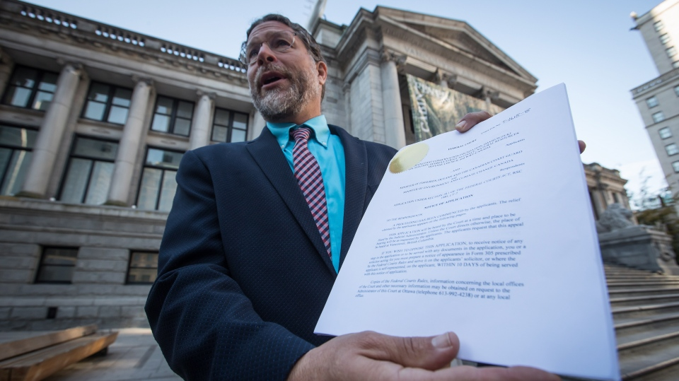 Jay Ritchlin, David Suzuki Foundation Director-General for Western Canada, holds a copy of a lawsuit conservation groups filed in federal court against Fisheries and Oceans Canada regarding the protection of southern resident killer whales, during a news conference in Vancouver, on Wednesday September 5, 2018. (The Canadian Press//Darryl Dyck)