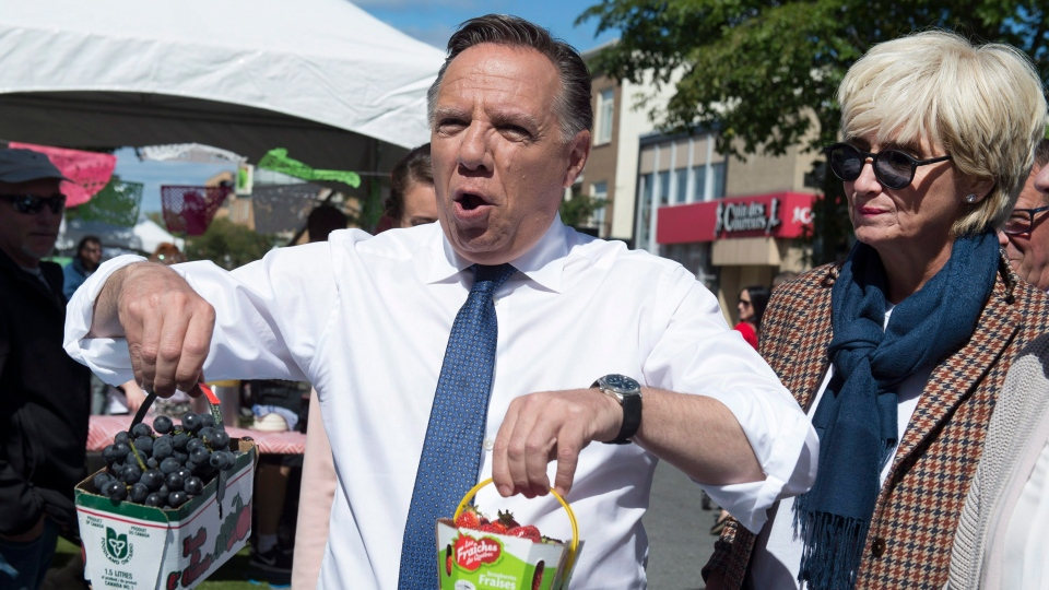 "Coalition Avenir Quebec Leader Francois Legault jokingly uses strawberries and grapes, saying ""let's go from red to blue"" while campaigning, Saturday, September 8, 2018 in Quebec City. Legault's wife Isabelle Brais, right, looks on. (Jacques Boissinot/ The Canadian Press)"