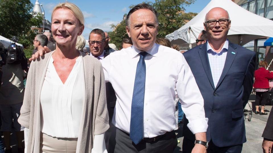 Coalition Avenir Quebec Leader Francois Legault walks with local candidates Svetlana Solomykina, left, and Mario Asselin, right, while campaigning, Saturday, September 8, 2018 in Quebec City. THE CANADIAN PRESS/Jacques Boissinot