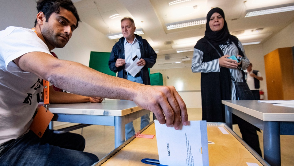 An Electoral counselor posts an election envelope in a polling station in Malmo, Sweden, Sunday Sept. 9, 2018. (Johan Nilsson/TT via AP)