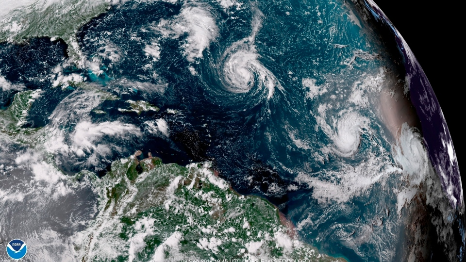 This enhanced satellite image made available by NOAA shows Tropical Storm Florence, center, in the Atlantic Ocean on Saturday, Sept. 8, 2018 at 2:45 p.m. EDT. (NOAA via AP)