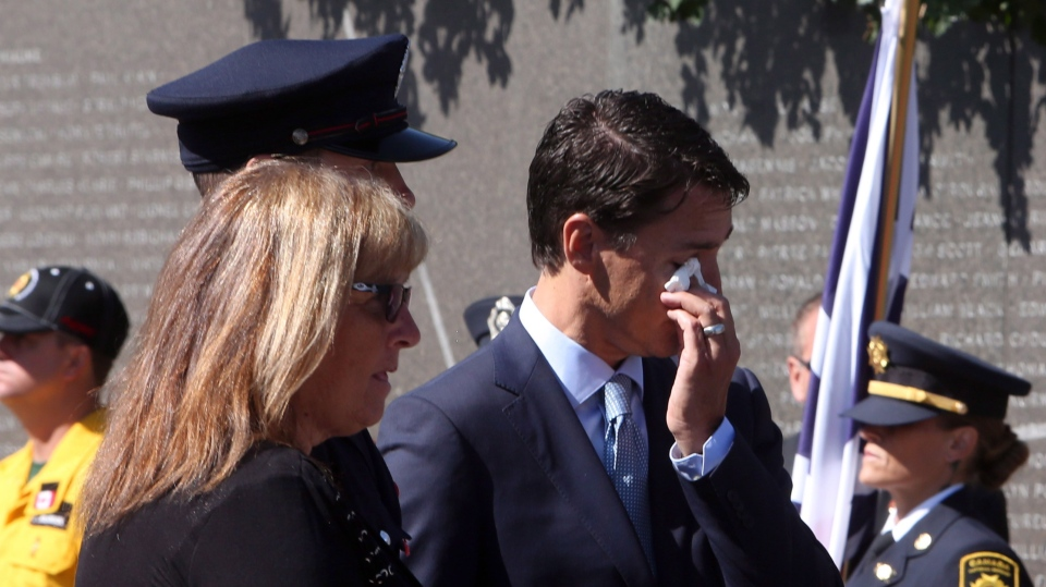 Prime Minister Justin Trudeau (right) wipes a tear as Rose Cassidy, wife of fallen firefighter Fire Chief Clayton Cassidy of the Cache Creek. B.C. Fire Department, takes part in the Firefighters' National Memorial Day ceremony at the Canadian Firefighters Memorial in Ottawa on Sunday, September 9, 2018. (Fred Chartrand/ The Canadian Press)