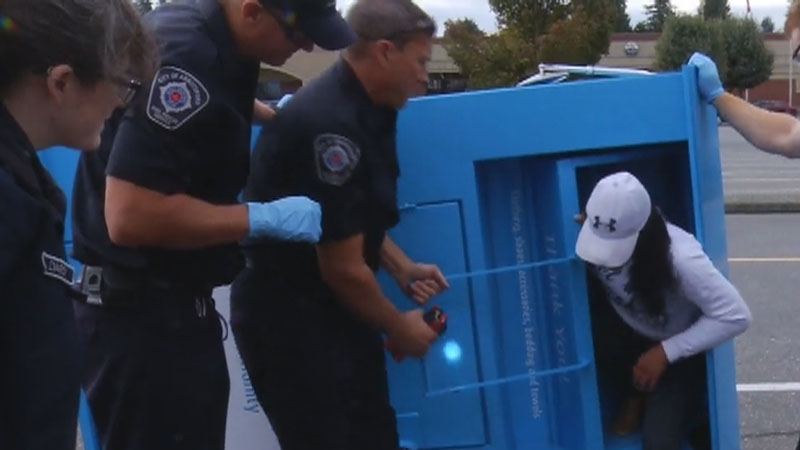 First responders lowered a donation bin, allowing a woman climb out of it.