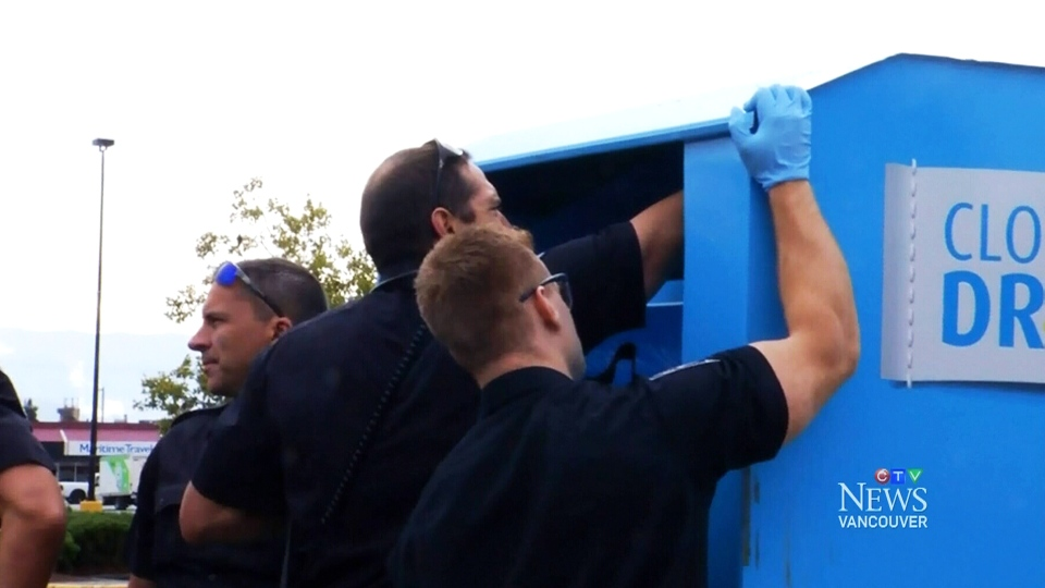 Firefighters peer inside a clothing donation bin in Abbotsford, B.C., before helping a woman trapped inside the box get to safety.