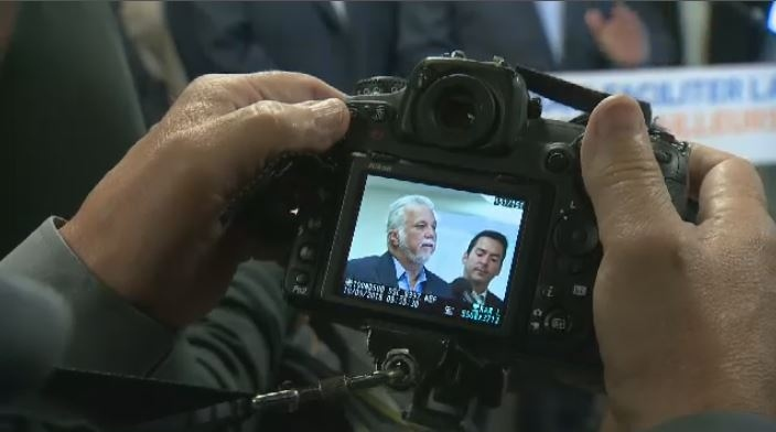 Liberal Party leader Philippe Couillard is pictured through the viewfinder of a photographer's camera as he spoke to reporters during the party's press briefing Monday morning. (CTV Montreal)