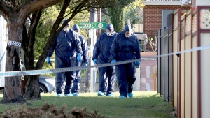 In this Sunday, Sept. 9, 2018 photo, forensic police officers inspect a property in suburban Perth, Australia. (AAP Image / Richard Wainwright)