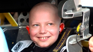 11-year-old Caleb Hammond grins before heading out in a stock car designed for children on the Southern Iowa Speedway dirt track in Oskaloosa, Iowa, Aug. 18, 2018. (Angie Holland, Oskaloosa Herald via AP)