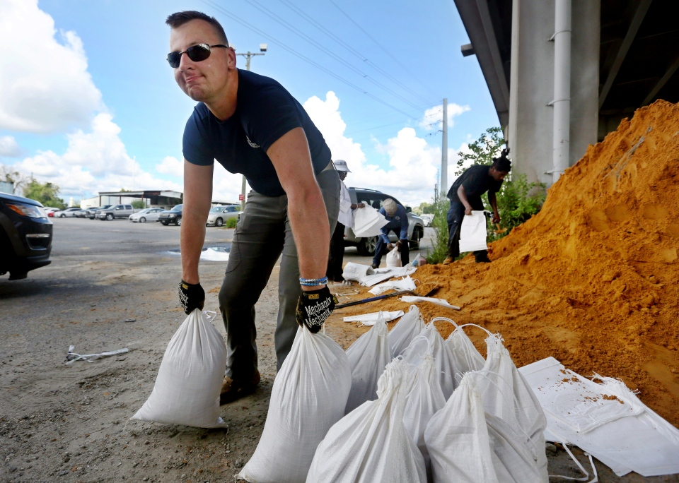 Kevin Orth loads sandbags into cars on Milford Street as he helps residents prepare for Hurricane Florence, Monday, Sept. 10, 2018, in Charleston,S.C. (Grace Beahm Alford/The Post And Courier via AP)