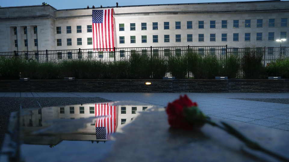 A U.S. flag is unfurled at sunrise on Sept. 11, 2018, at the Pentagon on the 17th anniversary of the Sept. 11th attacks. (Pablo Martinez Monsivais / AP)