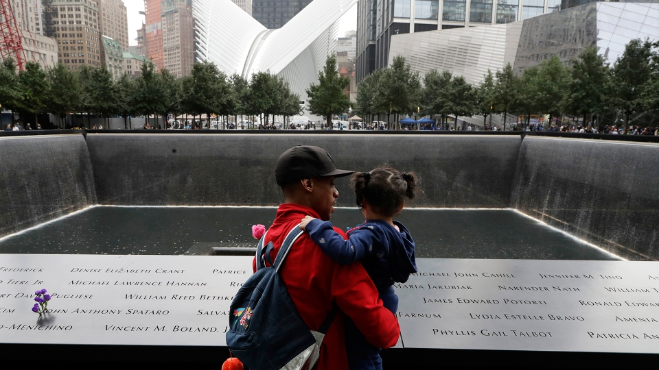 A man talks with a girl as they look at the North Pool at the World Trade Center during a ceremony marking the 17th anniversary of the terrorist attacks on the United States, Tuesday, Sept. 11, 2018, in New York. (AP / Mark Lennihan)