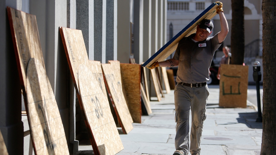 Preston Guiher carries a sheet of plywood as he prepares to board up a Wells Fargo bank in preparation for Hurricane Florence in downtown Charleston, S.C., Tuesday, Sept. 11, 2018. (AP / Mic Smith)