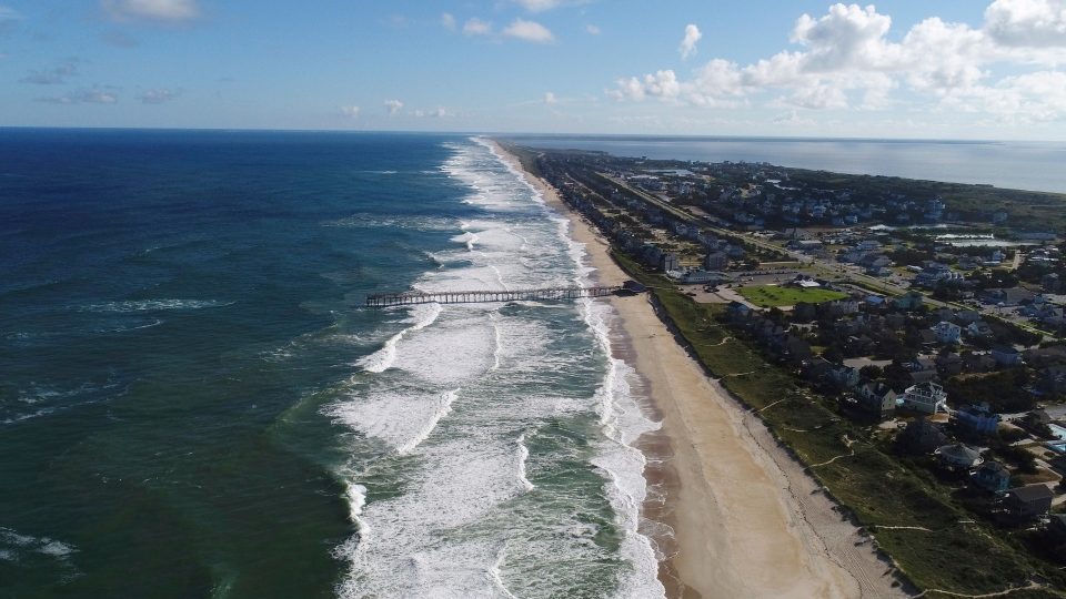 In this Monday afternoon, Sept. 10, 2018 photo provided by DroneBase, waves crash along Avon, N.C., in the Outer Banks ahead of Hurricane Florence. (DroneBase via AP)
