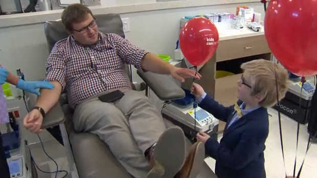 Foster Garrison, a six-year-old with leukemia, hands a balloon to a blood donor as a gesture of his gratitude on September 11, 2018
