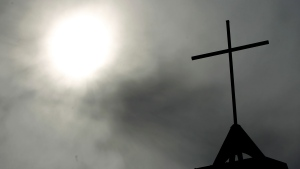 In this April 8, 2010 file photo a cross sits on top of a church in Berlin, Germany. (AP Photo/Markus Schreiber, File)