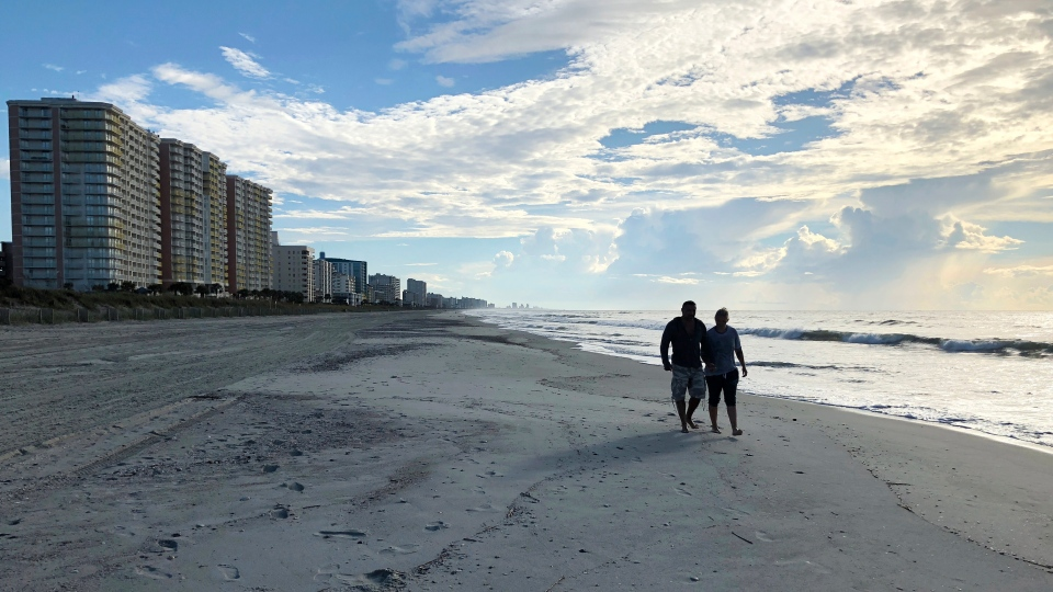Chris and Nicole Roland walk down a beach in North Myrtle Beach, S.C. on Wednesday, Sept. 12, 2018. (AP Photo/Jeffery Collins)