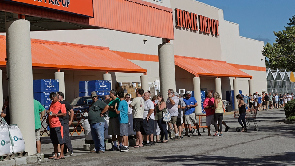 People line up outside a Home Depot for a new supply of generators and plywood in advance of Hurricane Florence in Wilmington, N.C., Wednesday, Sept. 12, 2018. (AP Photo/Chuck Burton)