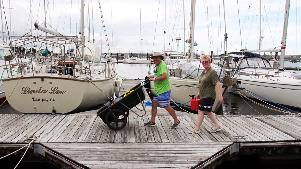 Danny and Doris Galli cart items from their boat docked at New Bern Grand Marina on the Trent River in New Bern, N.C, Tuesday, Sept. 11, 2018. Boat owners are preparing for expected storm surges as Hurricane Florence approaches eastern North Carolina. (Gray Whitley/Sun Journal via AP)
