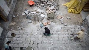 In this Monday, Sept. 10, 2018 photo, masons relay centuries-old paving stones in the courtyard of 25 Manzanares Street, in Mexico City. (AP / Eduardo Verdugo)