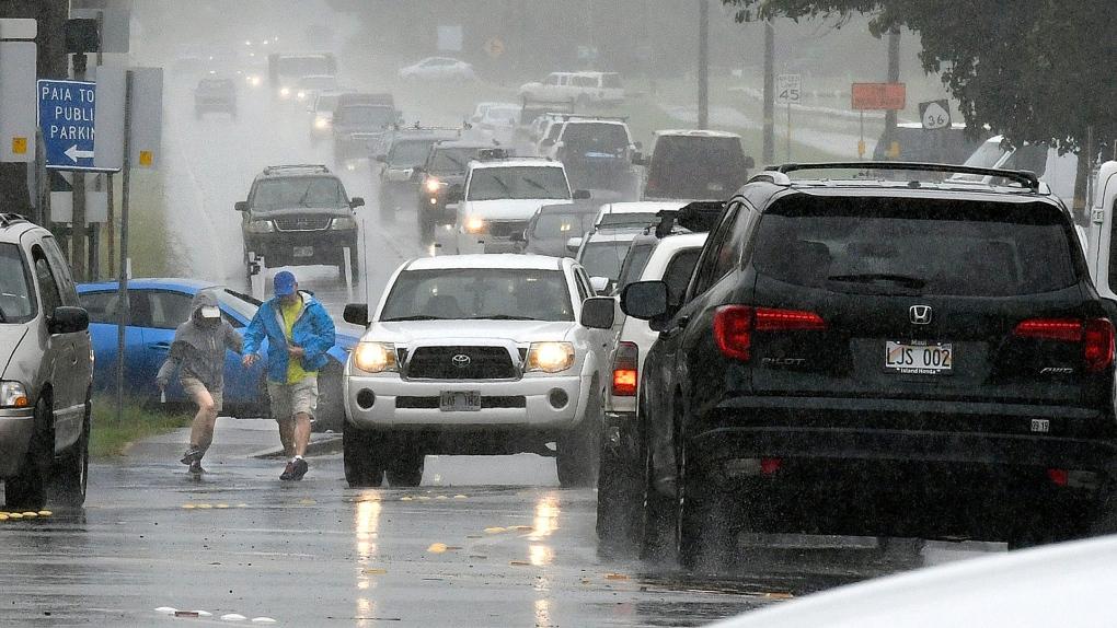 A couple walks in a rainstorm in Hawaii