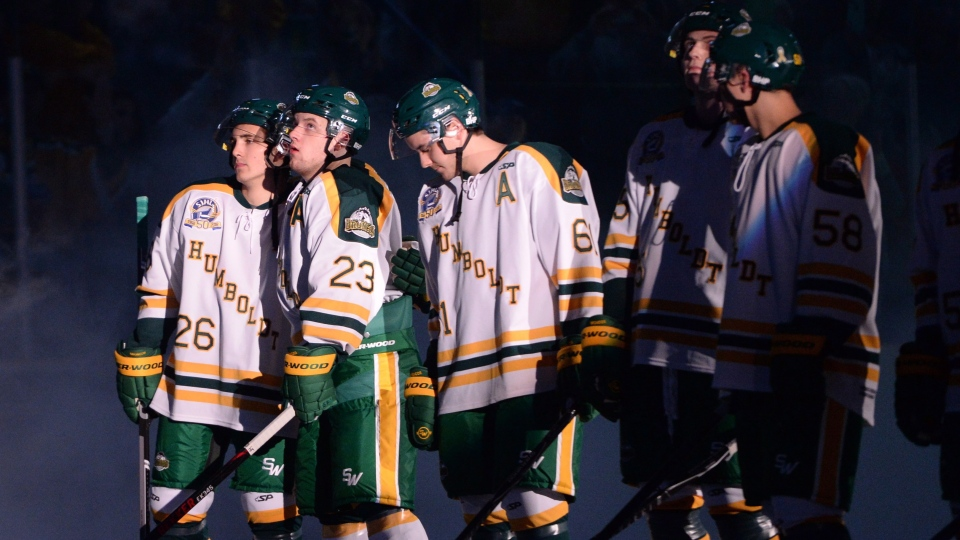 Returning Humboldt Broncos players Brayden Camrud (26) and Derek Patter (23) hug as they take part in the pregame ceremony before playing the Nipawin Hawks in the SJHL season home opener Wednesday, Sept. 12, 2018. (THE CANADIAN PRESS/Jonathan Hayward)