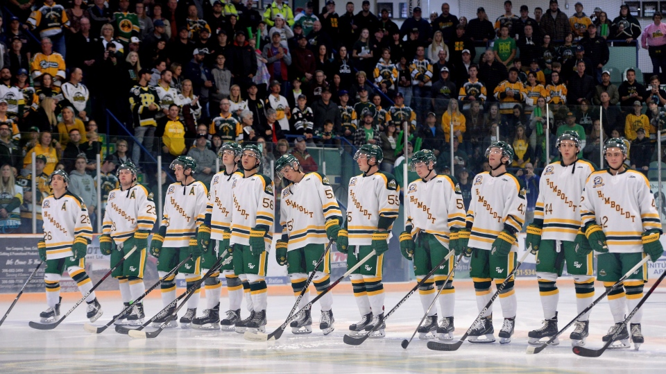 Returning Humboldt Broncos players Brayden Camrud (26) and Derek Patter (23), far left, take part in the pregame ceremony along with other teammate before playing the Nipawin Hawks in the SJHL season home opener Wednesday, Sept. 12, 2018. THE CANADIAN PRESS/Jonathan Hayward