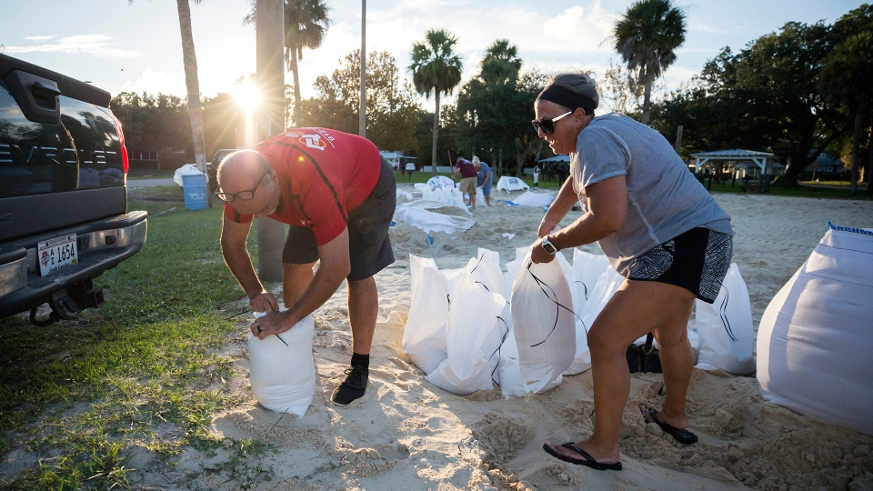 Filling sandbags with sand provided by the City of Tybee Island, Sib McLellan, left, and his wife, Lisa McLellan, prepare for Hurricane Florence, Wednesday, Sept., 12, 2018 on Tybee Island, Ga. (AP / Stephen B. Morton)