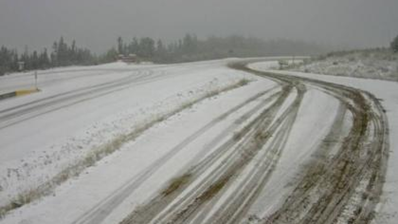 Snow is seen on Highway 97 west of Fort Nelson in this image from B.C. Transportation. (Twitter)