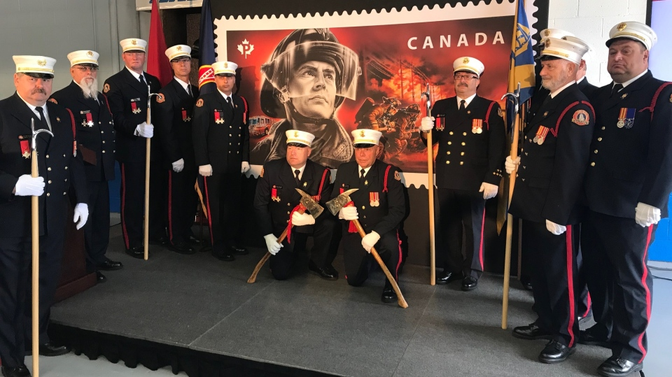 Firefighters with Halifax Regional Fire and Emergency help unveil a stamp honouring Canada's firefighters on Sept. 13, 2018.