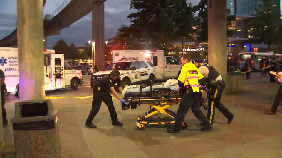 A youth is carried away on a stretcher after a stabbing near the Surrey Central SkyTrain Station on Sept. 12, 2018.