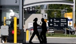 Canadian border guards are silhouetted as they replace each other at an inspection booth at the Douglas border crossing on the Canada-USA border in Surrey, B.C., on August 20, 2009. THE CANADIAN PRESS/Darryl Dyck
