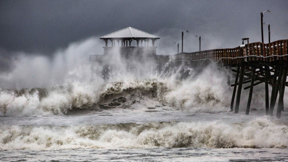Waves slam the Oceana Pier and Pier House Restaurant in Atlantic Beach, N.C., Thursday, Sept. 13, 2018 as Hurricane Florence approaches the area. (Travis Long/The News & Observer via AP)