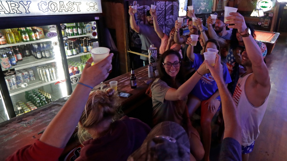 Locals riding out the storm toast Hurricane Florence as they relax at the Barbary Coast bar in downtown Wilmington, N.C., on Thursday, Sept. 13, 2018. (AP Photo/Chuck Burton)