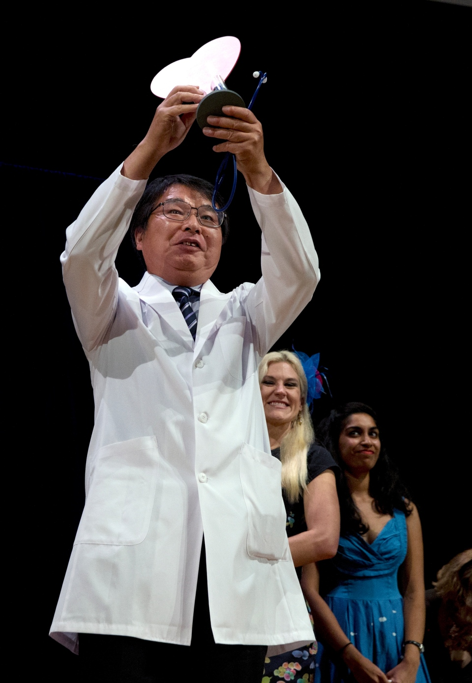 Akira Horiuchi, of Japan, holds up his Ig Nobel for medical education during award ceremonies at Harvard University in Cambridge, Mass., Thursday, Sept. 13, 2018. Horiuchi won for devising a revolutionary new way to give yourself a colonoscopy. (AP Photo/Michael Dwyer)