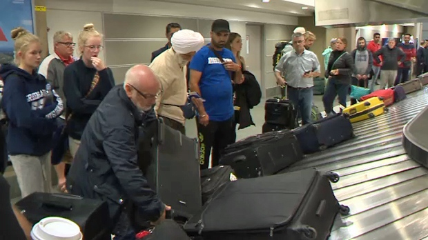 British Airways passengers collect their luggage at Calgary International Airport on September 13, 2018 following an unexpected overnight stop in Nunavut