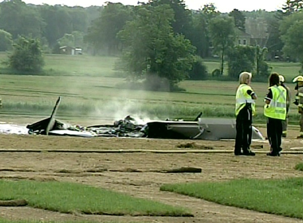 Emergency workers look at the smoking wreckage of a small plane that crashed near Ontario's Waterloo International Airport on Monday, June 29, 2009.
