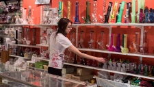 A store assistant reaches for a bong on a retail shelf at the Hotbox Cafe in Toronto on Saturday, January 20, 2018. (THE CANADIAN PRESS/Chris Young)