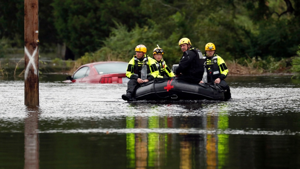 Members of a swift water rescue team check a flooded street caused by the tropical storm Florence in New Bern, N.C., on Saturday Sept. 15, 2018. (AP Photo/Chris Seward)