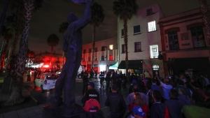 Curious onlookers gather on the perimeters of a crime scene after a shooting in Garibaldi Plaza in Mexico City, Friday, Sept. 14, 2018. (AP Photo/Stringer)
