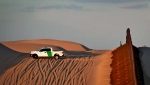 A U.S. Customs and Border Patrol agent patrols a section of floating fence at sunset that runs through Imperial Sand Dunes Wednesday, July 18, 2018 along the international border with Mexico in Imperial County, Calif. (AP Photo/Matt York)