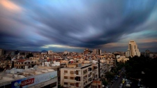 In this April 12, 2016 file picture taken with a slow shutter speed, clouds hover over the capital city of Damascus, Syria. (AP Photo/Hassan Ammar)