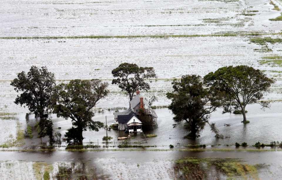 A farm house is surrounded by flooded fields from tropical storm Florence in Hyde County, N.C., Saturday, Sept. 15, 2018. (AP Photo/Steve Helber)