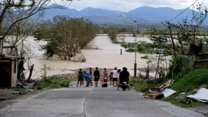 Residents stand by a flooded road following the onslaught of Typhoon Mangkhut in Tuguegarao city in Cagayan province, northeastern Philippines, Saturday, Sept. 15, 2018. (AP Photo/Aaron Favila)