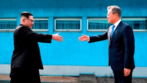 In this April 27, 2018, file photo, North Korean leader Kim Jong Un, left, prepares to shake hands with South Korean President Moon Jae-in over the military demarcation line at the border village of Panmunjom in Demilitarized Zone. (Korea Summit Press Pool via AP)