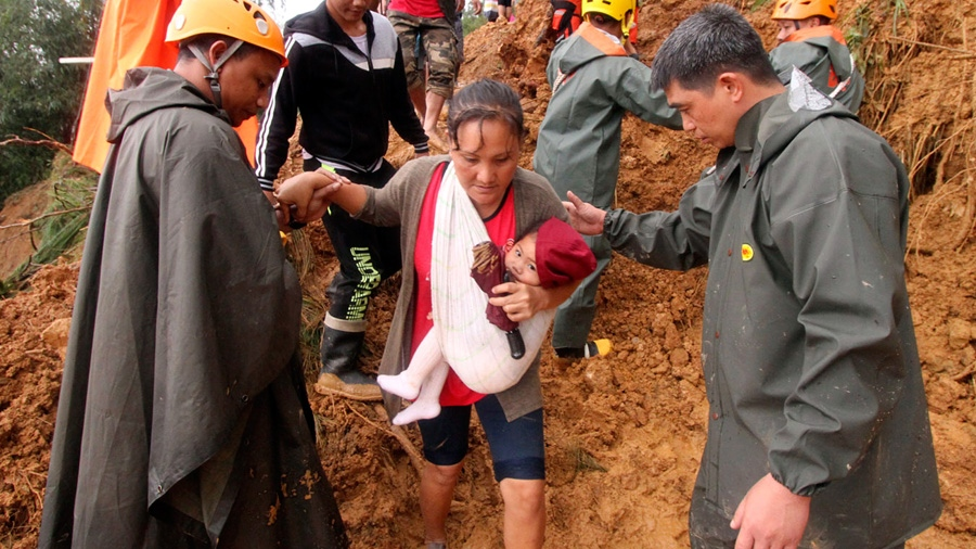 Rescuers assist a mother and her child as they evacuate to safer grounds following landslides that hit Itogon township, Benguet province in the northern Philippines due to Typhoon Mangkhut Sunday, Sept. 16, 2018.  (AP Photo/Jayjay Landingin)