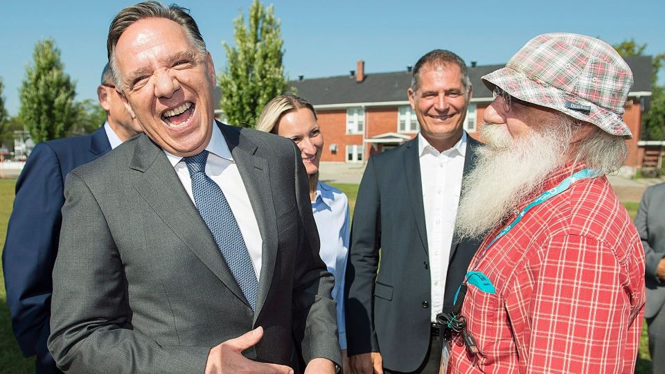 CAQ leader Francois Legault, left, laughs as he meets a supporter during a campaign stop in Coteau-du-Lac, Que., Sunday, September 16, 2018. (THE CANADIAN PRESS/Graham Hughes)