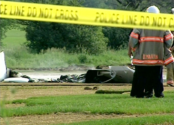 A firefighter stands next to the wreckage of a small plane that crashed near Ontario's Waterloo International Airport on Monday, June 29, 2009.